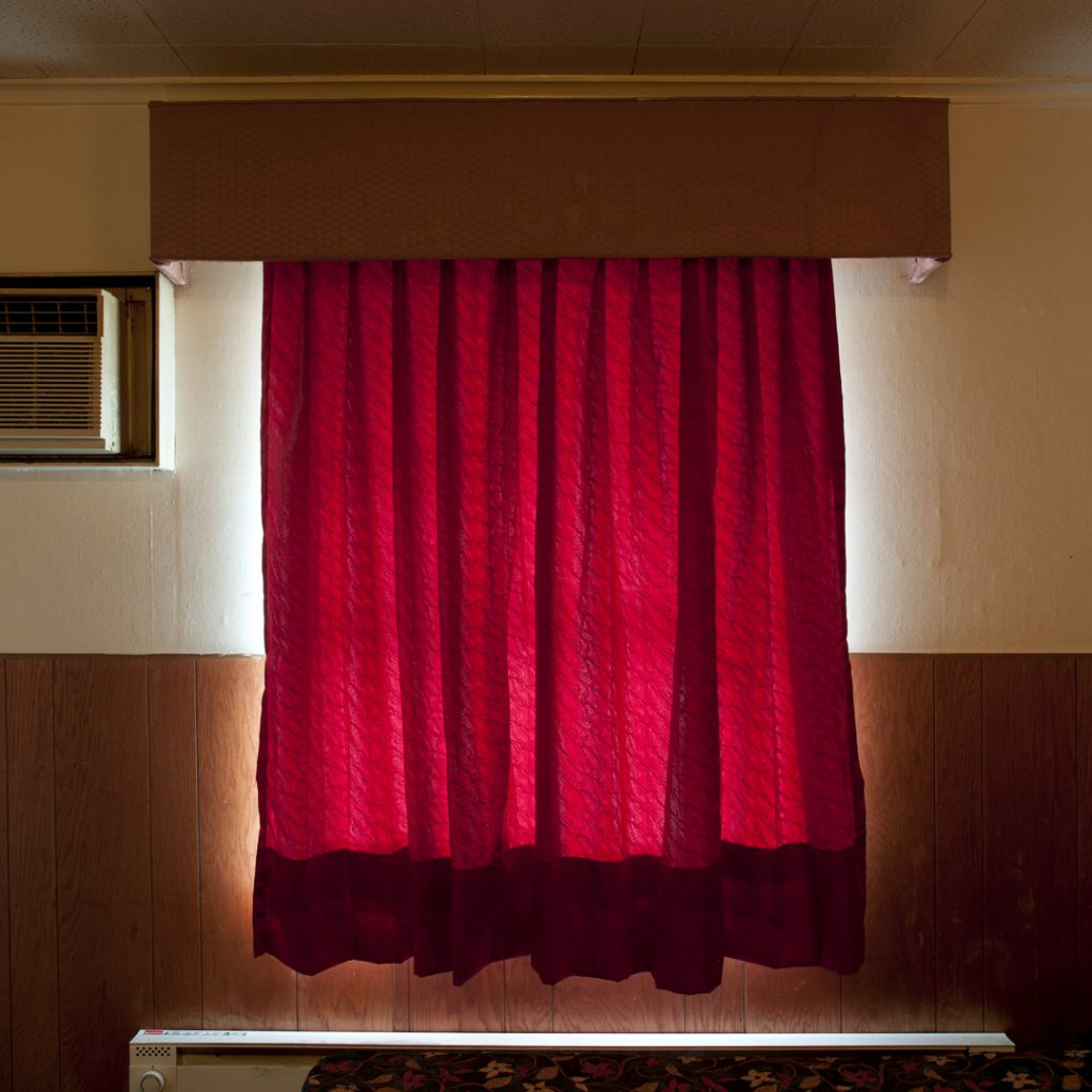 Photo of red curtains blocking light from outside.